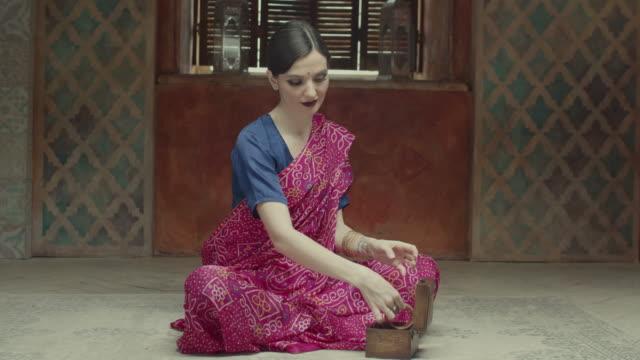 elegant indian style woman putting bracelets on - sari filmów i materiałów b-roll