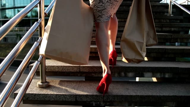 elegant legs of woman with shopping bags on stairs - shoes fashion stock videos and b-roll footage