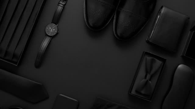 Elegant man clothes concept. Set of black wardobe and accessories for official party evening meeting Elegant man clothes concept. Set of black wardobe and accessories for official party or evening meeting. Placed on black backgound. With shirt, shoes, watch, bow, tie. Top view. Flat lay with copy space. businesswear stock videos & royalty-free footage