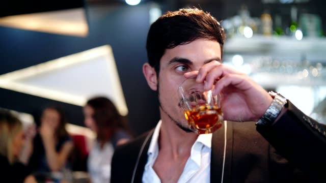 elegant man drinking whiskey in the bar - scotch whisky video stock e b–roll