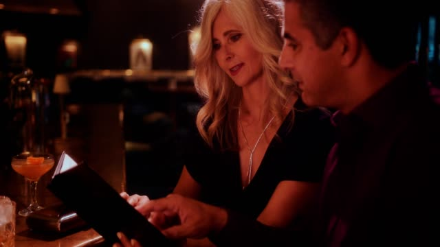 Elegant mature couple reading menu at luxurious bar and restaurant