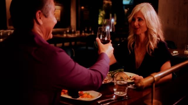Elegant mature couple toasting and drinking red wine at restaurant