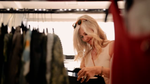 衣料品店で服を買いにエレガントな熟女 - スタイリッシュ点の映像素材/bロール