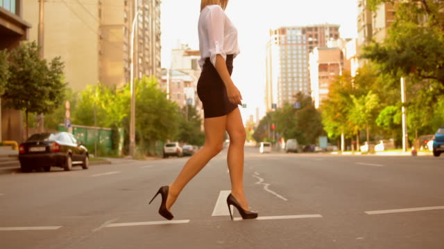 Elegant pedestrian in town Side view fashionable woman with blond hair wearing white shirt and black skirt and high-heels shoes walking on the road in summer city.slow motion beautiful woman stock videos & royalty-free footage