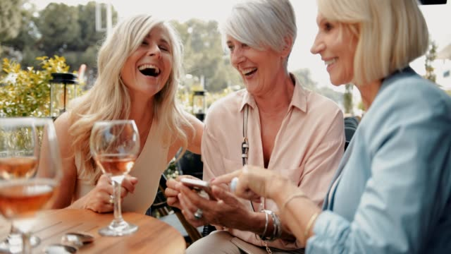 Elegant senior women drinking wine and using smartphone at restaurant Fashionable mature friends having fun, drinking wine, using smartphone and laughing together on restaurant patio mature women stock videos & royalty-free footage