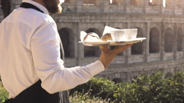 elegant smiling waiter serving breakfast with breakfast coffee croissant cappuccino on a try outdoor to a bar restaurant table in front of colosseum in rome at sunset - kelner filmów i materiałów b-roll
