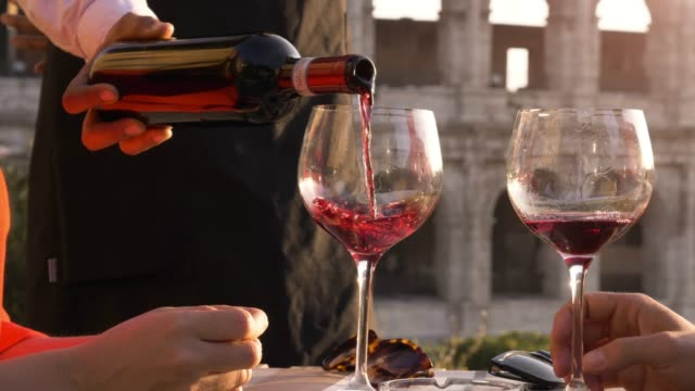 vídeos de stock e filmes b-roll de elegant waiter serving pouring glass of red wine to romantic couple sitting at restaurant table in front of colosseum in rome at sunset - vinho