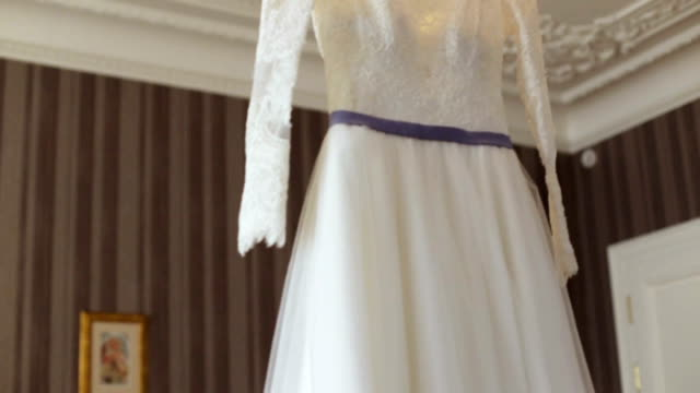 Elegant wedding dress on a hanger specially made for a wedding ceremony of a young bride. Elegant wedding dress on a  hanger specially made for a wedding ceremony of a young bride. tulle netting stock videos & royalty-free footage