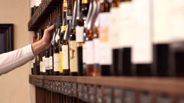 Elegant wine seller selecting wine for customers in wine shop
