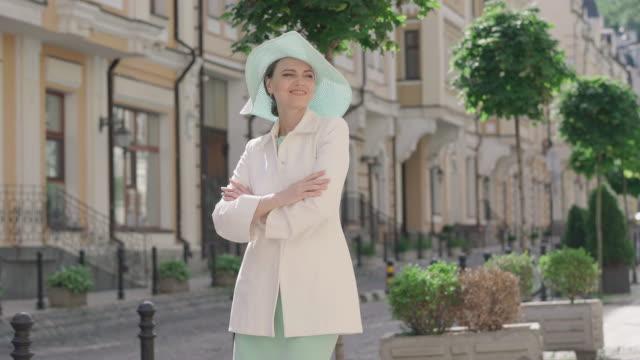 elegante frau genießen sonnigen tag in fremden stadt. porträt der charmanten kaukasischen touristin, die im freien steht und lächelt. glückliche dame in hut und weißem mantel posiert in europa-reise. - einzelne frau über 30 stock-videos und b-roll-filmmaterial