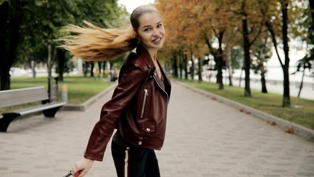 stockvideo's en b-roll-footage met elegante dame in jas burgundy leer maken luchtfoto kus wandelen in stad straat, slowmotion - paardenstaart haar naar achteren