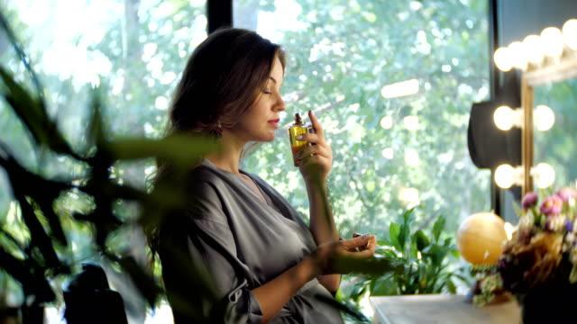vídeos de stock e filmes b-roll de elegant woman spraying herself with perfume - aromaterapia