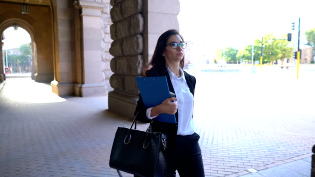Elegant woman walking under the building arch with clip folder in hand. video