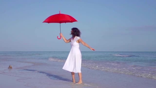 Elegant Woman Walking With Red Umbrella On Beach In White Dress video