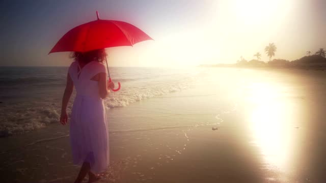 Elegant Woman Walking With Red Umbrella On Beach In White Dress