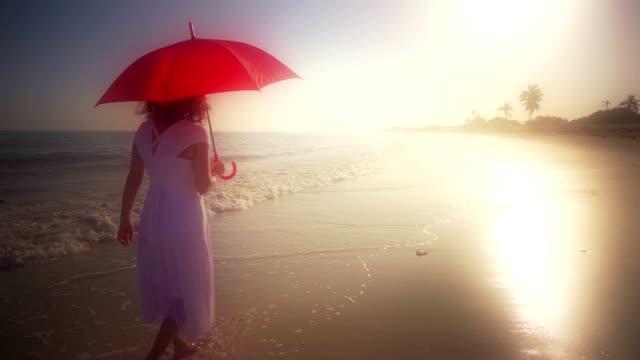 vídeos de stock e filmes b-roll de elegante mulher a andar com guarda-chuva vermelho na praia em vestido branco - guarda chuva