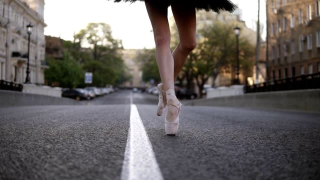 elegant young ballet dancer on the street on an empty road. stepping on tip toes in pointe. close up of a ballerina's legs. slow motion - cięcie w linii środkowej filmów i materiałów b-roll