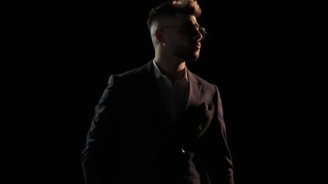 elegant young businessman in suit coming out of the dark. Man removing and putting on sunglasses, lookng around and going back elegant young businessman in suit coming out of the dark. Man removing and putting on sunglasses, lookng around and going back to the dark low lighting stock videos & royalty-free footage