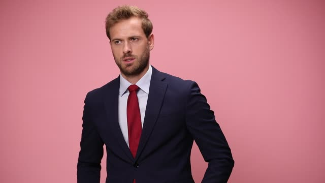elegant young businessman looking down and checking time, looking around, making faces, frowning, holding hands in pockets, nodding and refusing on pink background