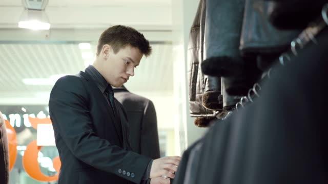 Elegant young man in suit choosing jacket in clothing store video