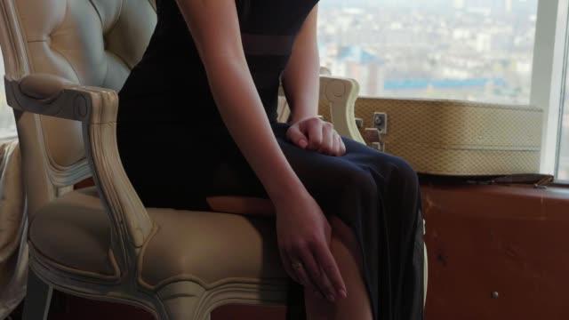 Mulher jovem elegante de vestido preto relaxante na cadeira perto da janela no lounge do hotel - vídeo
