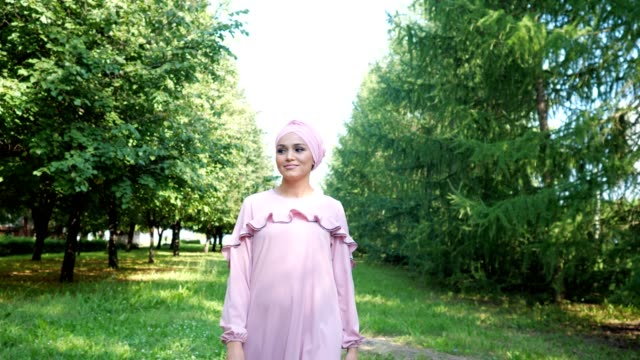 elegant young woman in designed purple dress with hijab - abbigliamento modesto video stock e b–roll