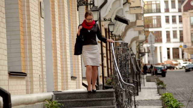 Elegant young woman in glasses walking on stone stairs video
