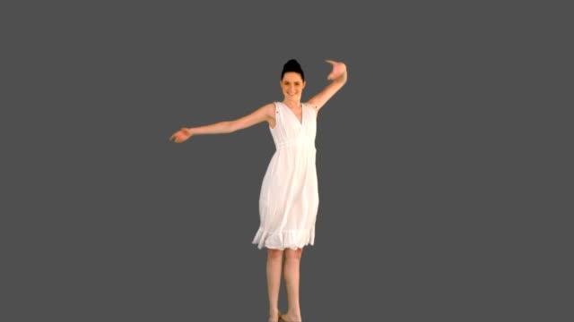 vídeos de stock e filmes b-roll de elegante jovem mulher de vestido branco saltar - cabelo preto