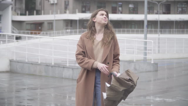 vídeos de stock e filmes b-roll de elegant young woman opening umbrella as it starts raining and running away. portrait of charming beautiful caucasian brunette girl on rainy day outdoors. lifestyle, weather, elegance. - chapéu