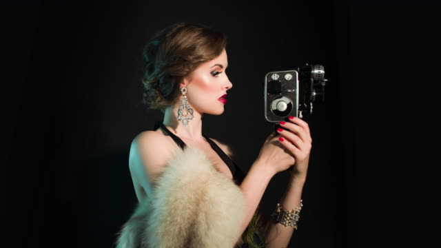 elegants woman with old movie camera - art deco architecture stock videos & royalty-free footage