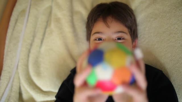 элементарный мальчик возраста, играющий с маленьким мячом в спальне, лежа на кровати - предподростковый возраст стоковые видео и кадры b-roll