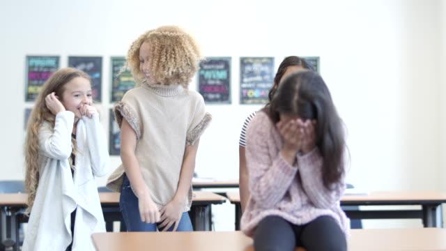 ragazza in età elementare vittima di bullismo da parte dei compagni di classe - preadolescente video stock e b–roll