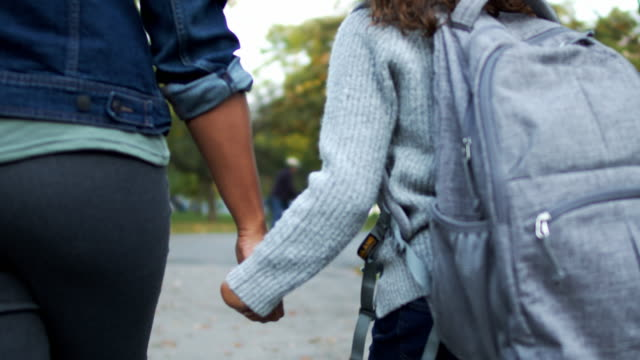 Elementary age girl holding her mother's hand while walking home from school