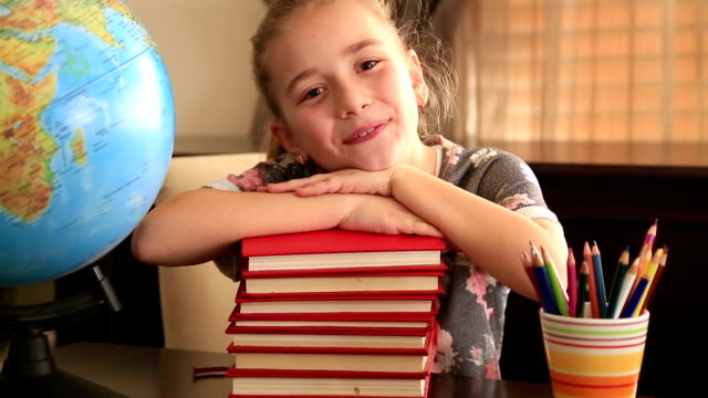 stockvideo's en b-roll-footage met elementary age girl posing on a stack of books. - e learning
