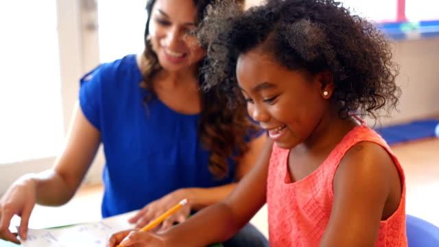 小学校低学年の女の子は、保育園で先生と数学の問題 ビデオ