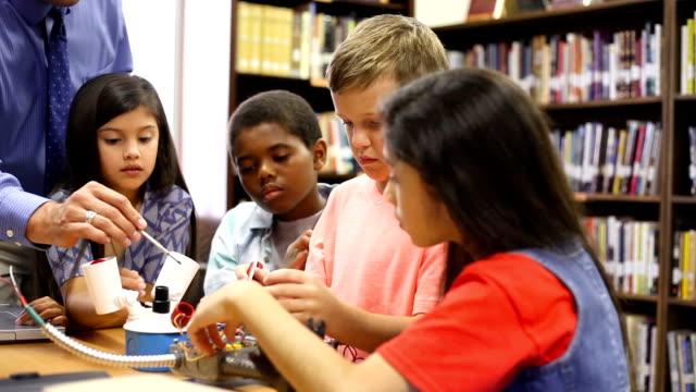 Meninas da escola elementar de idade construir robô na classe de tecnologia. - vídeo