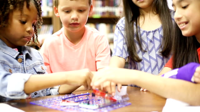 Elementary age school girls build robot in technology class. video