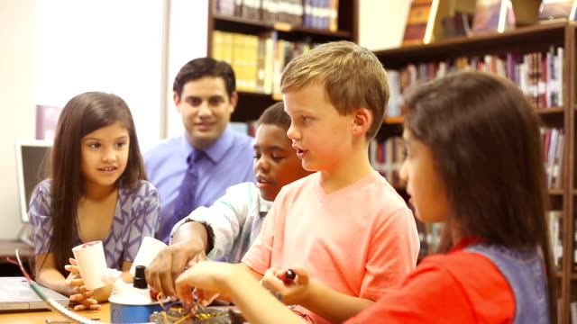 Elementary age school students build robot in technology class. video
