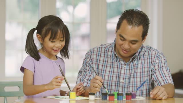 elementary åldern tjej gör konsthantverk med hennes far hemundervisning - filippinskt ursprung bildbanksvideor och videomaterial från bakom kulisserna