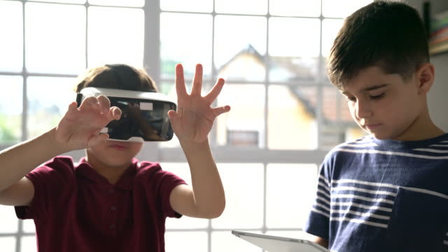 ragazzi delle elementari che usano le tecnologie in classe - scoprire nuovi terreni video stock e b–roll