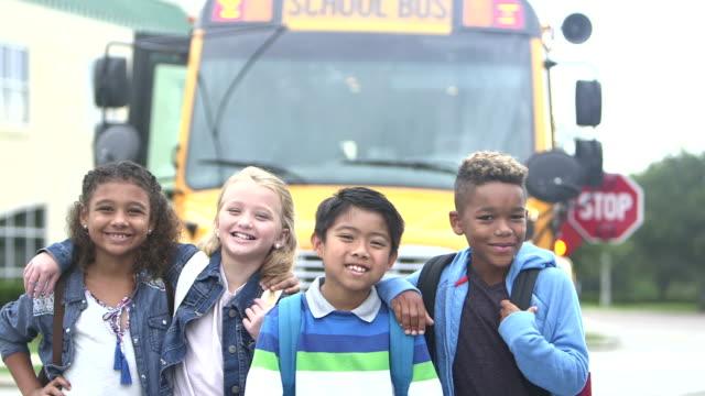 elementary children standing in front of school bus - viaggio d'istruzione video stock e b–roll