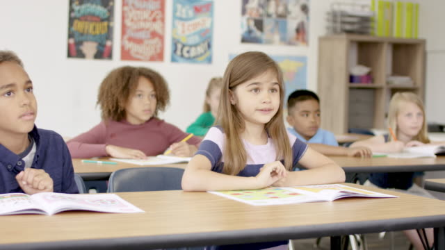 Elementary Children Working In Classroom A classroom full of elementary students sitting at desks are all engaged and working away in their workbooks. They appear to be happy about being in class. primary school stock videos & royalty-free footage