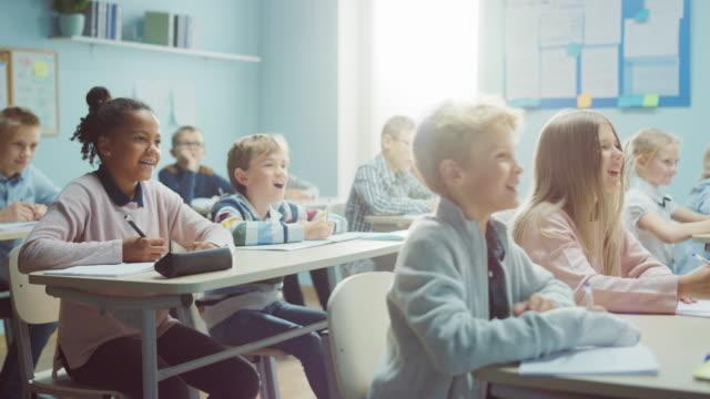 vídeos y material grabado en eventos de stock de aula de clase de diversos niños brillantes escuchando a su maestro dando lección, ríe juntos después de que dice algo divertido. niños jóvenes felices en la escritura de la escuela primaria en cuadernos de ejercicios - escuela media