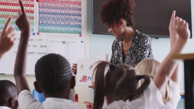 grundschüler in uniform hebt hand, um frage zu beantworten, wie lehrerin liest buch - lehrer stock-videos und b-roll-filmmaterial