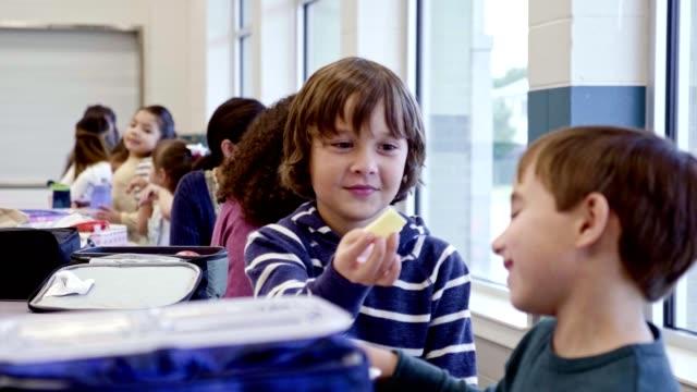 stockvideo's en b-roll-footage met basisschool jongens ruilen items van hun lunch - schooljongen