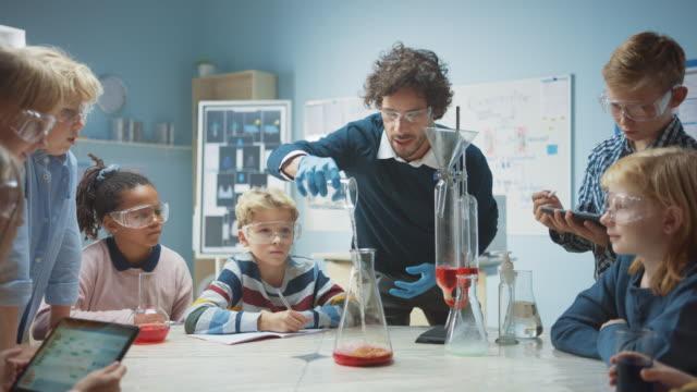 aula di chimica della scuola elementare: l'insegnante entusiasta insegna a diversi gruppi di bambini mostra un esperimento di reazione scientifica mescolando sostanze chimiche nel becher in modo che sparino schiuma (dentifricio di elefante) - gommapiuma video stock e b–roll