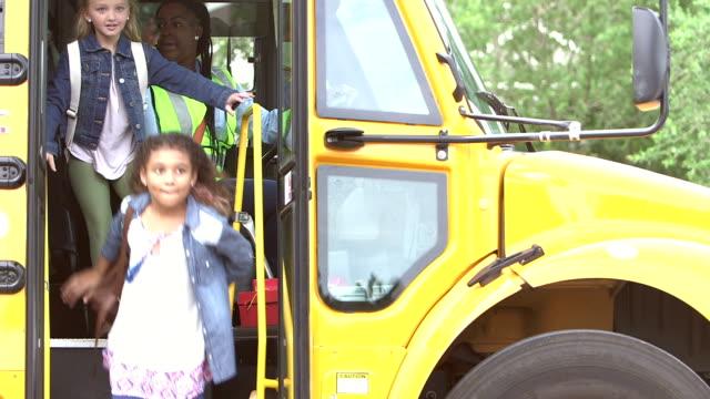 Elementary school children exit school bus