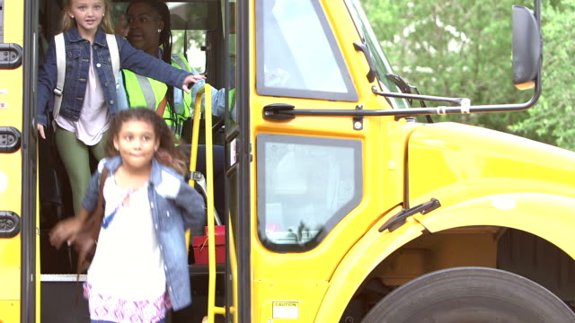 Elementary school children exit school bus A group of six multi-ethnic elementary school children, 7 to 9 years old, exit a yellow school bus. The driver opens the door, and waves to the students to go. After six disembark, she closes the door. elementary age stock videos & royalty-free footage