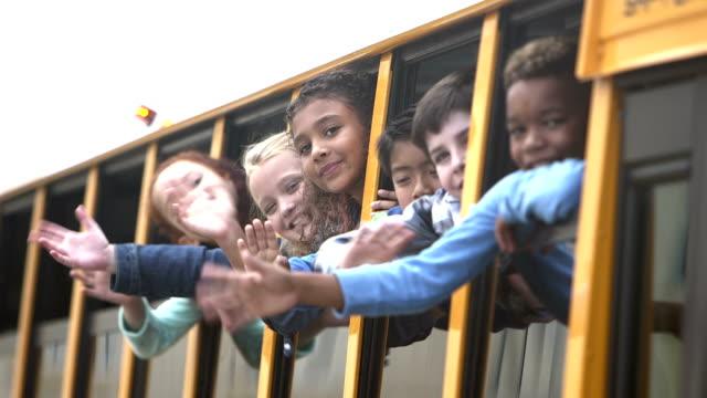 vidéos et rushes de enfants des écoles élémentaires bus fenêtre en agitant à l'affût - élève
