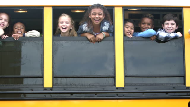 Elementary school children looking out bus windows
